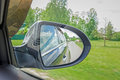 A view in the side view mirror. Mirror rear car. Reflection of the road Royalty Free Stock Photo