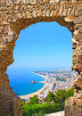 View of spanish beach through stone door in blanes costa brava a the st john castle resort town summertime catalonia spain Royalty Free Stock Images