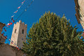 View of stone steeple tower next to church and tree in Vence. Royalty Free Stock Photo