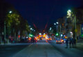View of the street in the city at night blurred, where riding cars, trams glow lights and vehicle headlights. Royalty Free Stock Photo