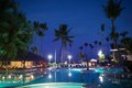 View of summer tropical resort at night with empty restautant huge palms and electric lights reflecting in the swimming pool in Stock Image