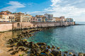 View of syracuse ortiggia sicily italy houses facing the sea panorama in morning in background blue sky and reflections on Royalty Free Stock Image