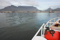 View of table mountain from fishing trawler a and the city cape town the deck a with orange fenders in the foreground Stock Photo