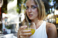 View though the window of a attractive female drinking a glass of fresh orange juice young happy caucasian woman enjoying natural Stock Image