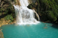 View to amazing waterfall with turquoise pool surrounded by gree Royalty Free Stock Photo
