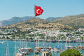 View to the marina with the Turkish National flag at the flagpole waving over a hill in Bodrum, Turkey. Royalty Free Stock Photo