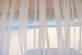 View to white tropical beach through transparent window curtain Royalty Free Stock Photo