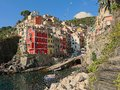 View of the town of Riomaggiore with colorful red and yellow houses on a cliff overlooking the sea, Royalty Free Stock Photo