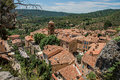 View of trees, house roofs and belfry under sunny blue sky in Moustiers-Sainte-Marie. Royalty Free Stock Photo