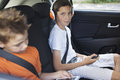 A view  on two boys sitting in a car playing tablet and listening to music Royalty Free Stock Photo