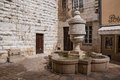 View of wall, fountain and shop in Vence. Royalty Free Stock Photo