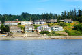 View of waterfront neighborhood a a beautiful small homes at low elevation on a slight hill under blue skies Stock Photography
