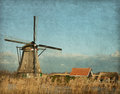 View of windmill at kinderdijk netherlands photo in retro style added paper texture Royalty Free Stock Image