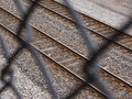 Viewing railroad tracks through chain link fence looking at Stock Photos