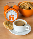 Vigorous breakfast the orange alarm clock cup of coffee and cookies are on a wood background Royalty Free Stock Images