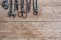 Viiew of vintage rusted tools on old wooden table: pliers, pipe wrench, screwdriver, hammer, metal shears, saws and other. Royalty Free Stock Photo