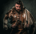 Viking with cold weapon in a traditional warrior clothes Royalty Free Stock Photo