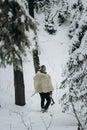 Viking hunter in pelt walking in snow winter forest with steel a