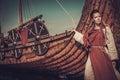 Viking woman standing near Drakkar on the seashore. Royalty Free Stock Photo