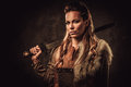 Viking woman with sword in a traditional warrior clothes, posing on a dark background. Royalty Free Stock Photo
