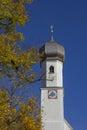 Village church in gmund, golden beech leaves and blue sky, bavar