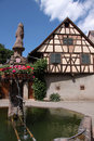 Village fountain with with half-timbered house Royalty Free Stock Photo