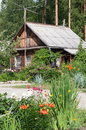 Village house near the flower beds Royalty Free Stock Image