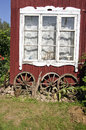 Village house old window with ancient horse carriage wheel Royalty Free Stock Photo
