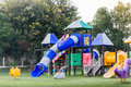Village public playground with colourful plaything for children in evening sunlight Stock Photo