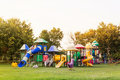Village public playground with colourful plaything for children in evening sunlight Royalty Free Stock Image