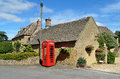 Village in rural england honey coloured stone houses and a red telephone box a the cotswolds Stock Photo