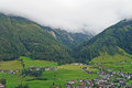 A village in the stubai valley in tyrol austria view on green houses and forested mountain slopes peaks clouds Royalty Free Stock Images