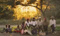 Villagers wait at a bus stop in rural zimbabwe africa group of people outlined sunlight patiently setting outside of bulawayo Royalty Free Stock Photo
