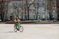 VILNIUS, LITHUANIA - April 10, 2012: Woman Riding Bike in Vilnius, Lithuania. Cathedral Square Royalty Free Stock Photo