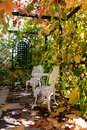 Vine-covered porch with hammered furniture at autumn Royalty Free Stock Photo