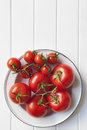 Vine tomatoes in rustic bowl enamel over white timber lots of copy space Royalty Free Stock Photos