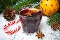 Vinho ferventado com especiarias picante no vidro nos doces da neve e do caramelo Fotografia de Stock