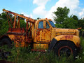 Vintage abandoned rusty yellow truck an antique work sits rusting and in a wooded area with weeds and flowers Stock Images
