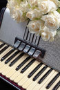 Vintage accordion and a bouquet of white roses. Concept of a nostalgic music. Royalty Free Stock Photo