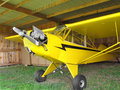 Vintage airplane in hanger close up of a small yellow single engine an old Stock Photography