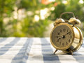 Vintage alarm clock on blue plaid tablecloth. The background is green from tree and light bokeh Royalty Free Stock Photo