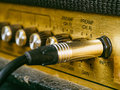 Vintage amplifier input macro photo of a electric guitar showing the knobs and plug selective focus on the word Stock Photo