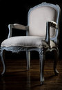 Vintage armchair beige color with carved legs Stock Image