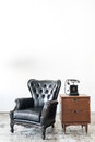 Vintage armchair and telephone on white wall. Royalty Free Stock Photo