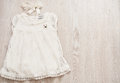 Vintage Baby White Lace Dress and Bow Headband on a Light Gray Wodden Background. Top View, Copy Space