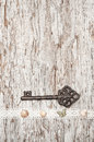 Vintage background with old key and lacy cloth on wood