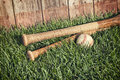 Vintage baseball and bats on grass near old wooden fence Royalty Free Stock Photo