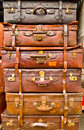 Vintage battered leather suitcases stacked vertically Royalty Free Stock Photography