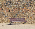 Vintage bench near stone wall Stock Images