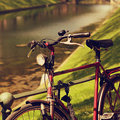 Vintage bicycle in the park near the fence on river bright sunny Royalty Free Stock Photo